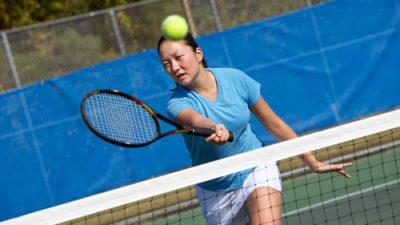 Woman playing tennis on hard court