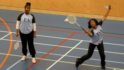 Two young women playing badminton in a sports hall
