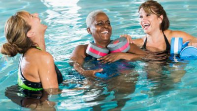 Three women swimming with flotation devices in a pool