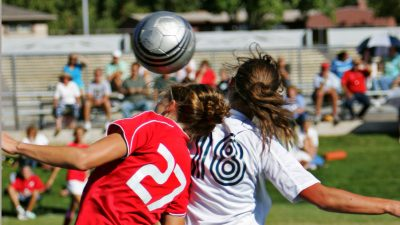 Female footballers challenging for a header