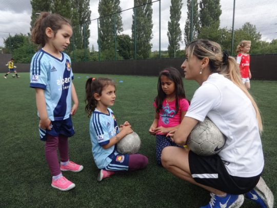 Manisha Tailor and three young girls on a football pitch