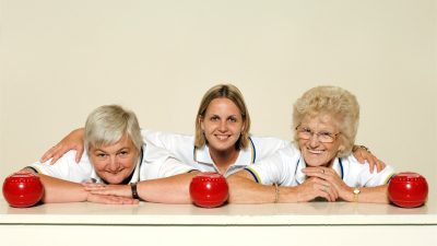 Three female members of a bowls club posing for a photo with each other