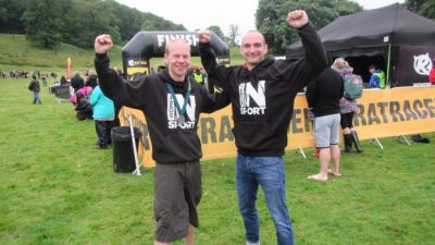 Two men at running event wearing Women in Sport hoodies