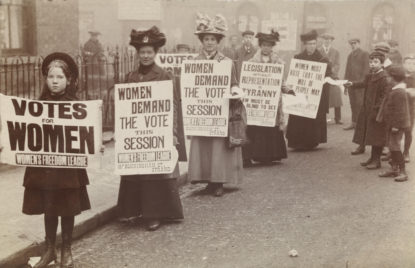 Women stand in gutter for poster parade to promote suffrage message