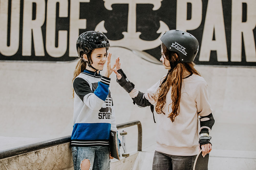 Girls high fiving each other while skateboarding