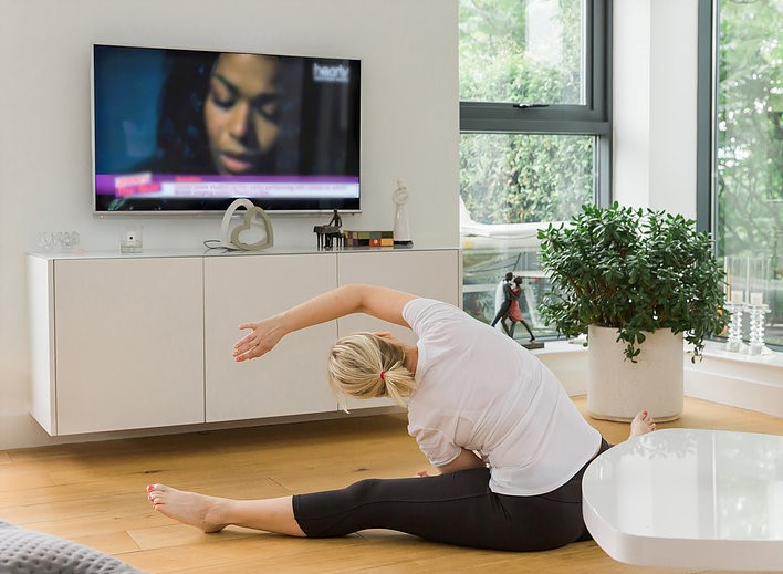 Woman stretching in front of television
