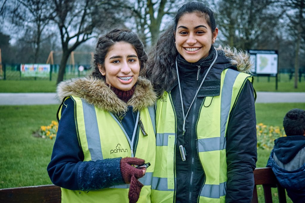 Two teenage girls in high vis vests volunteering at parkrun
