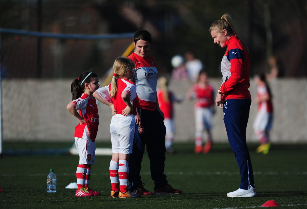 Professional female footballers talking to young girl players
