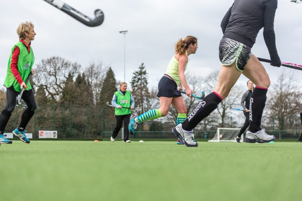 Female hockey players on green pitch