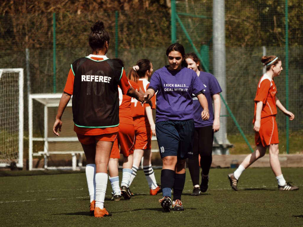 Women shaking hands before a football match