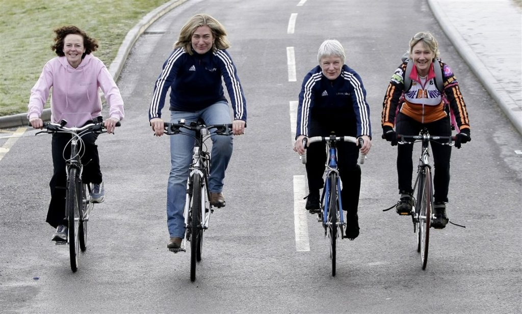 Group of women in casual clothes riding bikes