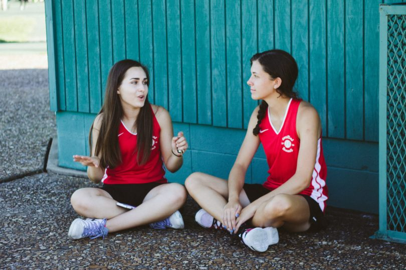 Two girls in sports kit sit cross-legged talking