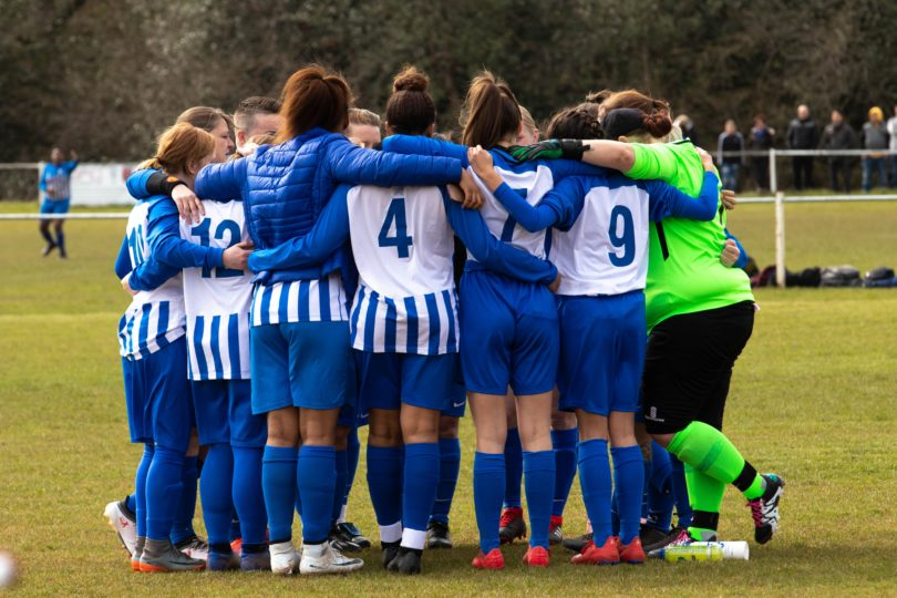 Women's football team in a huddle in blue kit