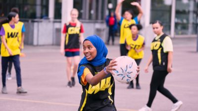 girl in hijab holding netball about to pass to her team