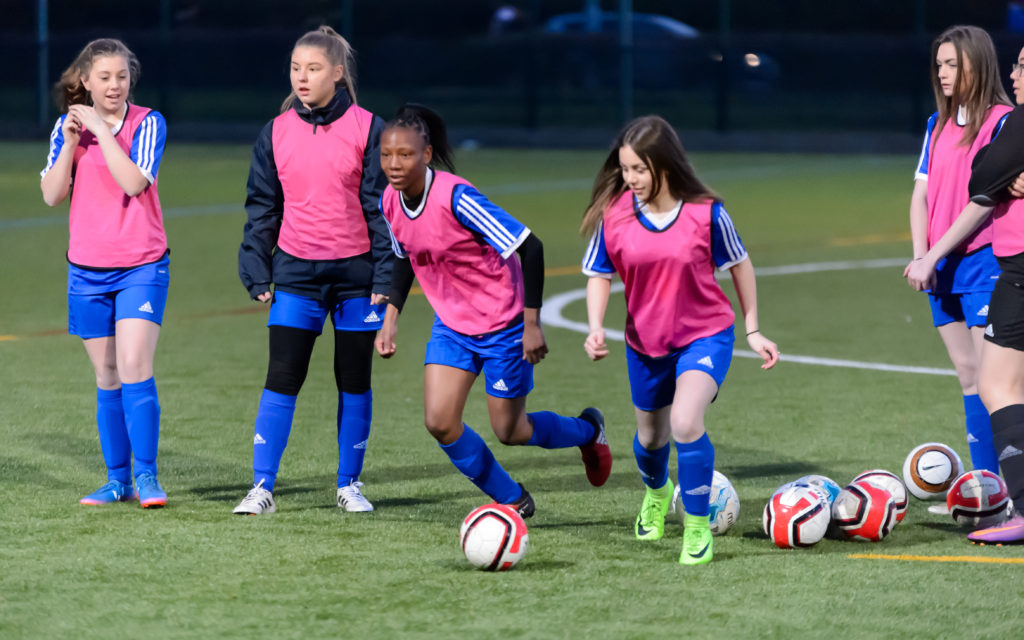 Girls playing football with pink bibs