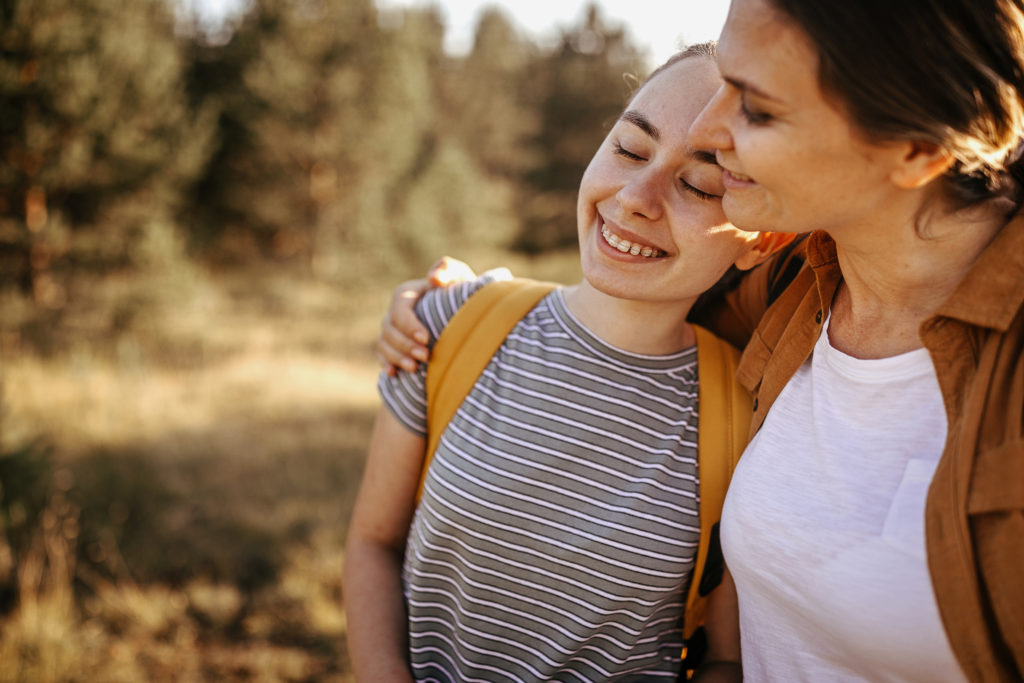 Loving mother and daughter embracing on hiking tour