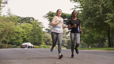 two girls running together in a park
