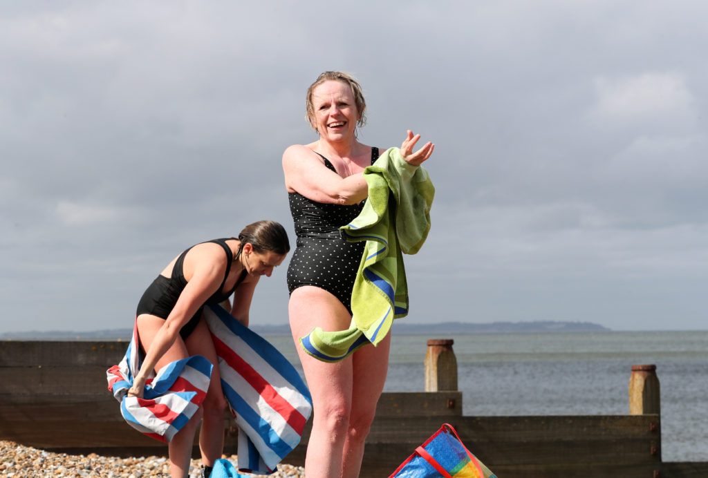 woman in swimsuit dries herself on a towel on the beach