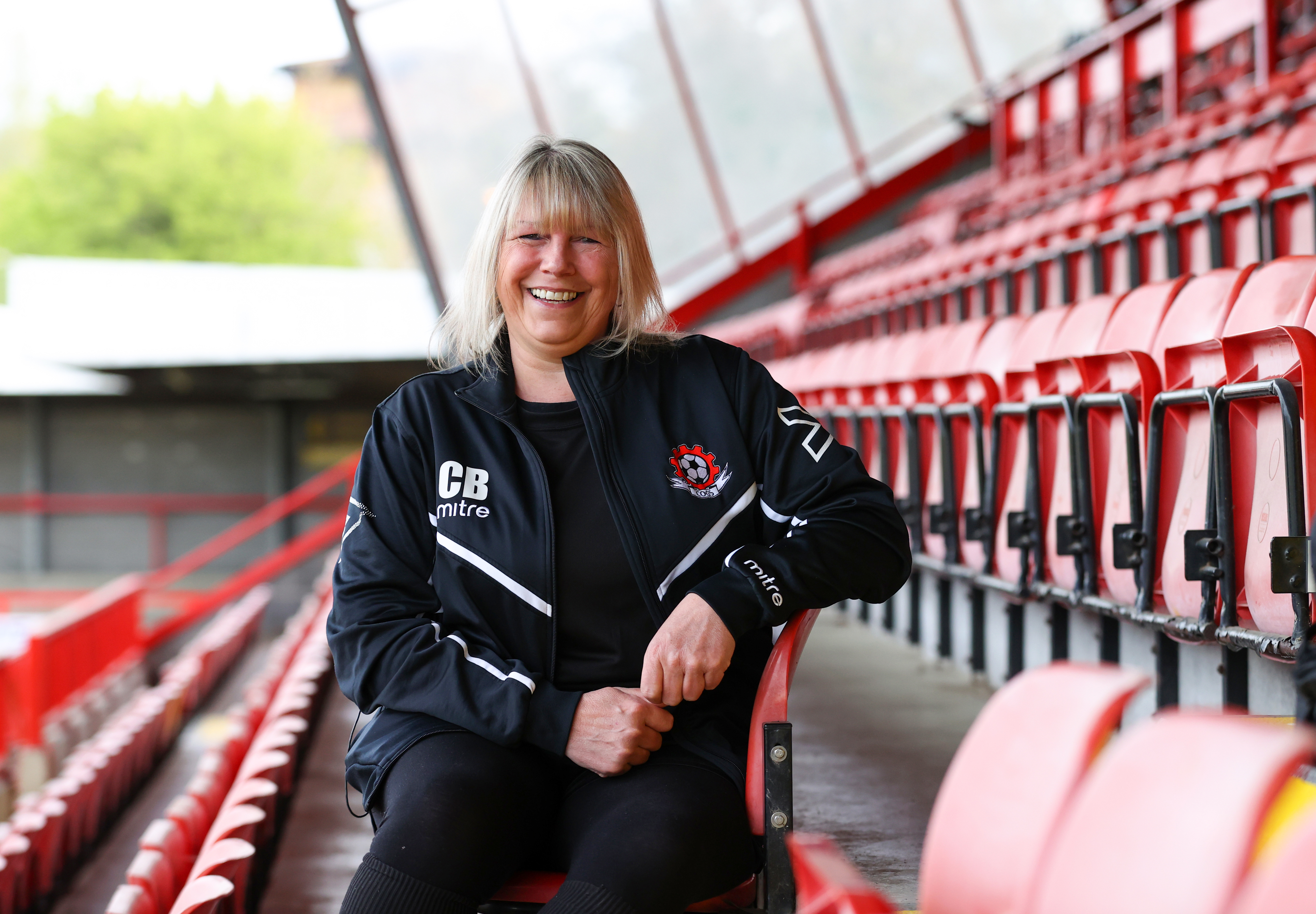 smiling woman sitting in football stands