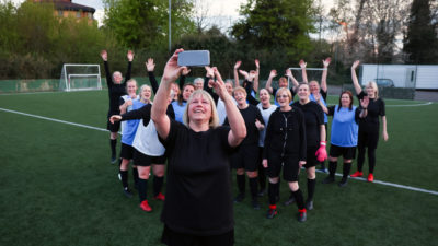 woman taking selfie on her phone with football team of women standing behind her
