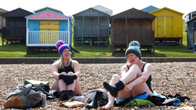 women in swimsuits and bobble hats sitting on a shingle beach in front of beach huts