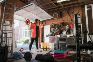 woman in orange jacket lifts a barbell on her shoulders in her garage