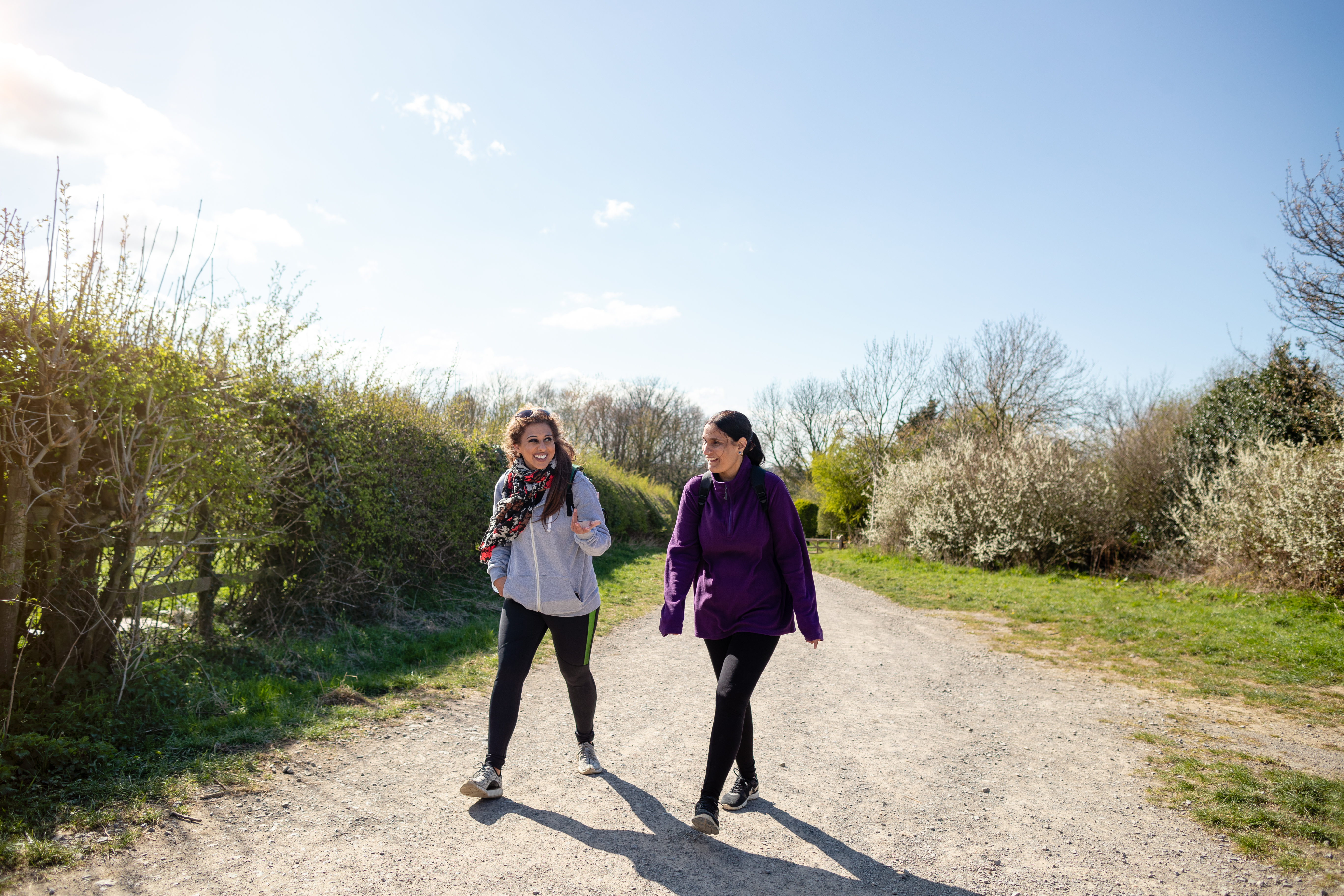 Two women walk side by side along a gravel road, sunshine, blue skies and green hedges on either side
