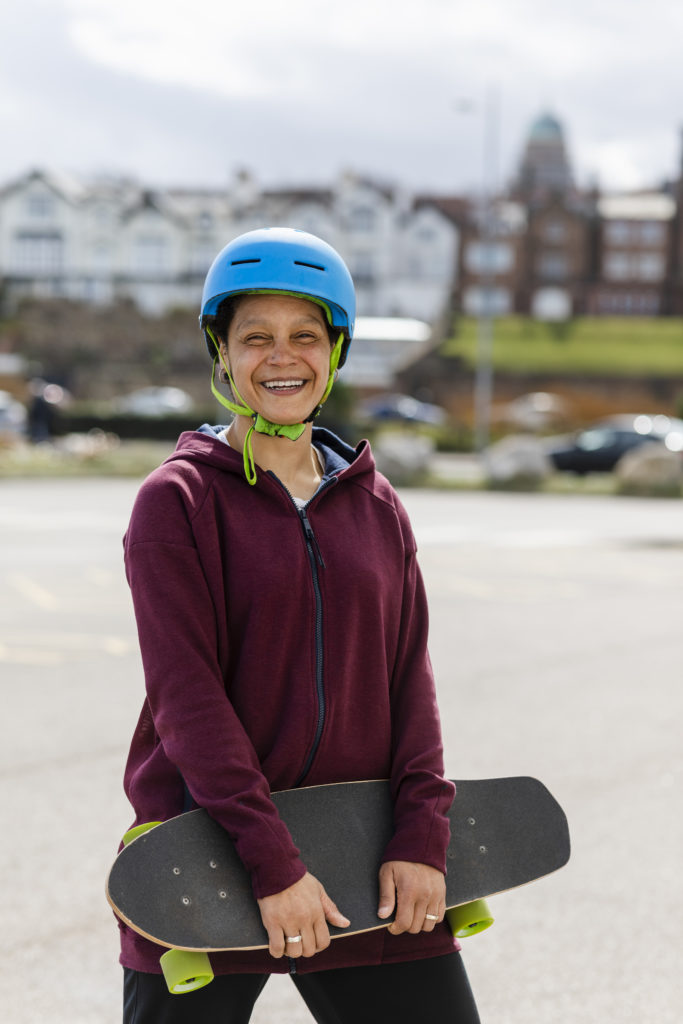 woman with blue helmet stands holding a skateboard and smiling