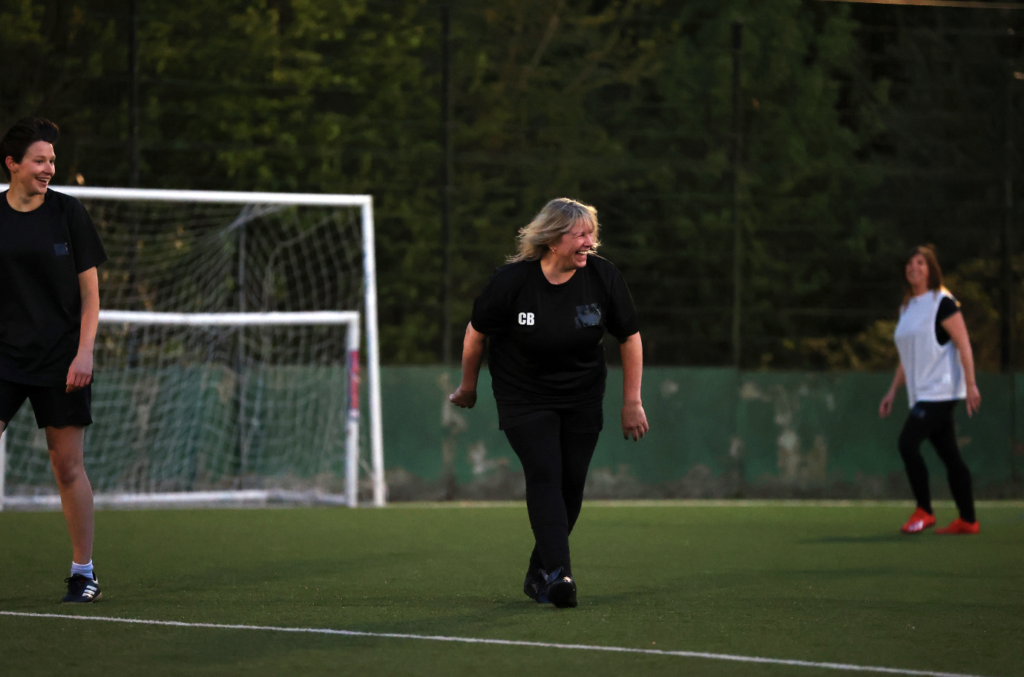 woman in black fitness kit walks on a football pitch