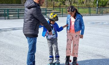 Father with daughter and son, helping them to roller skate